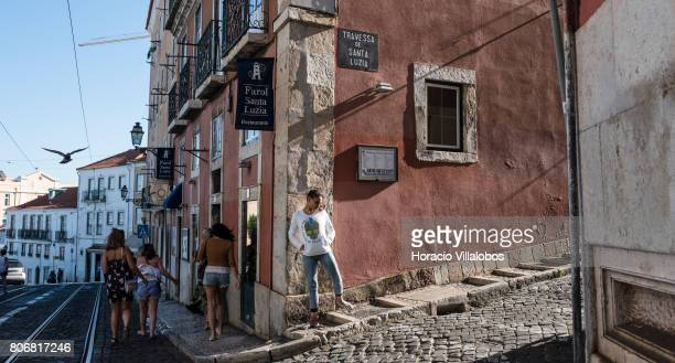 Tourists walk by Largo Santa Luzia near the castle of Sao Jorge in Bairro do Castelo neighborhood one of the city's oldest district and a favorite...