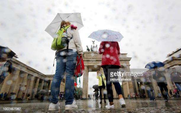 Tourists walk by the Brandeburg Gate under pouring rain and temperatures of 16 degreees Celsius in Berlin Germany 26 July 2017 According to...