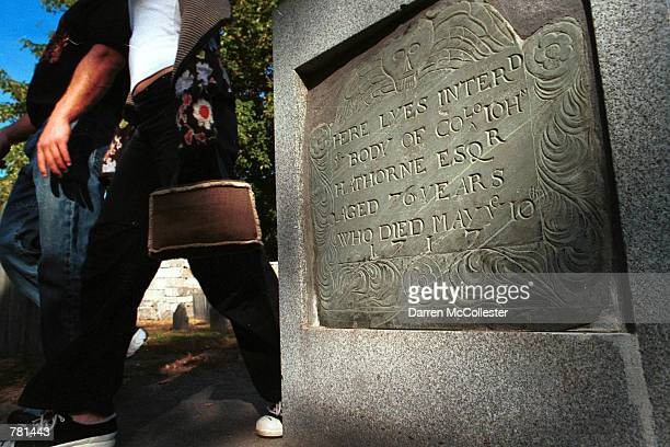 Tourists walk by the gravestone of Judge John Hathorne October 26 2000 in the nations second oldest graveyard in Salem MA Hathorne presided over the...