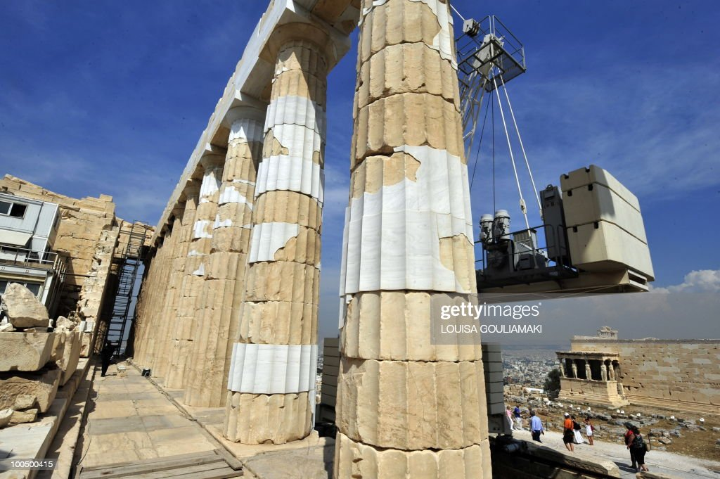 Tourists walk by the restored 5th century B.C.doric columns of the Parthenon temple, bearing contemporary, white marble pieces, at the Athens Acropolis on May 25, 2010. Greek state employees hijacked a restoration event at the Acropolis in Athens on Tuesday as the government tries to force through unpopular wage cuts and hiring freezes to cut massive debt. Around 200 culture ministry staff staged a protest at the Acropolis, Greece's best-known ancient monument, to demand permanent jobs after being hired on short-term contracts for years. AFP PHOTO / Louisa Gouliamaki