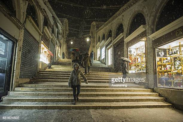Tourists walk during the snowfall at Rialto Bridge on January 13 2017 in Venice Italy A heavy snowfall hit Venice after the high tide of this morning...
