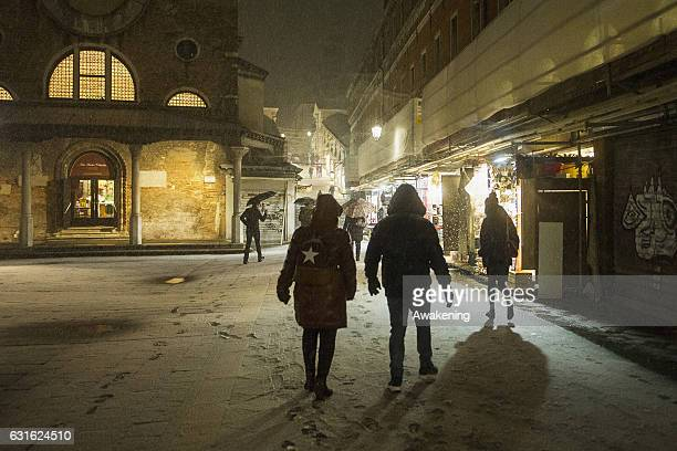 Tourists walk during the snowfall next to Rialto Bridge on January 13 2017 in Venice Italy A heavy snowfall hit Venice after the high tide of this...