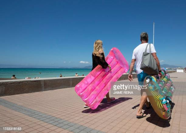 Tourists walk holding inflatable mattress at Palma Beach in Palma de Mallorca on June 7, 2021. - Spain opened its borders to vaccinated travellers...