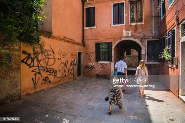 Tourists walk in a calle to reach St Mark square from railway station where there are graffiti and tags on the walls through San Polo district on...