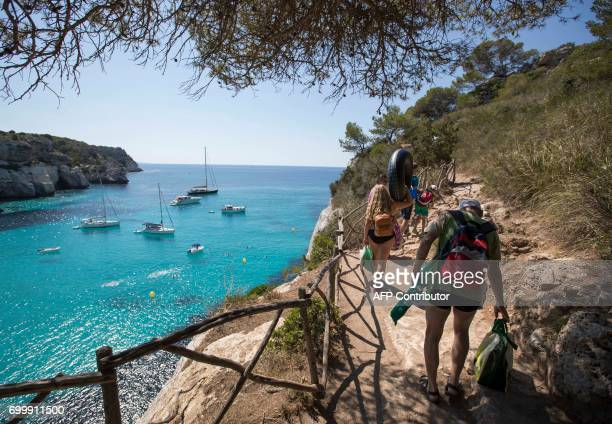 Tourists walk in Cala Mararella in Ciutadella with boats in background on the Menorca Island on June 22 2017 / AFP PHOTO / JAIME REINA