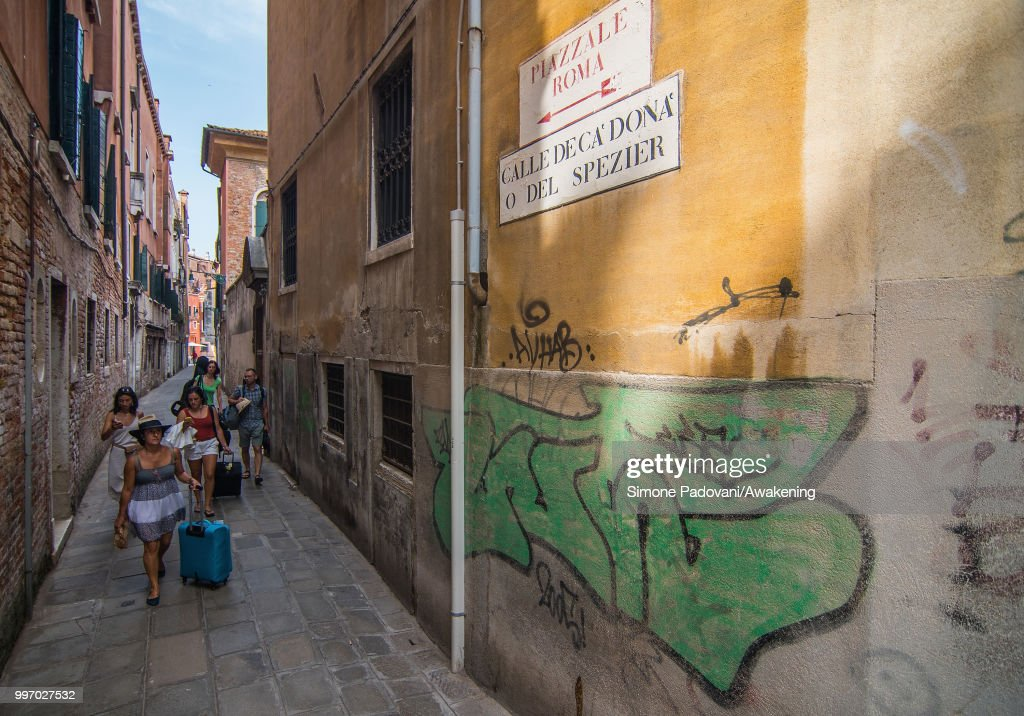 Tourists walk in Calle De Ca' Donà, where there are graffiti and tags on the walls, on the way that connects the bus station, Piazzale Roma, to Rialto bridge, through Santa Croce district, on July 12, 2018 in Venice, Italy. The plague of graffiti and tags on the walls of the palaces of Venice continues with new writing across the doors, windows and the plaster of shops, banks, historic buildings, ruining and attacking the priceless architectural heritage of the lagoon. Venice has been living with this problem for years, but it has not reached a resolution until today.