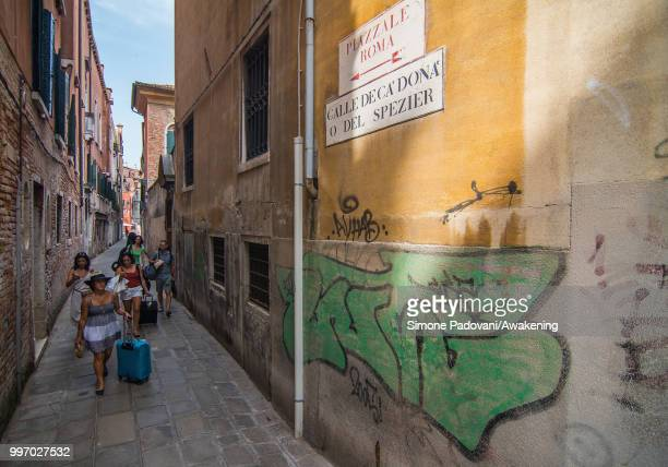 Tourists walk in Calle De Ca' Donà where there are graffiti and tags on the walls on the way that connects the bus station Piazzale Roma to Rialto...