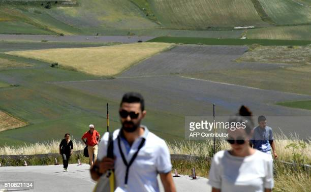 Tourists walk in Castelluccio, a small village in central Italys Umbria region on July 8, 2017. After the hearthquake in Octber 2016 the road...
