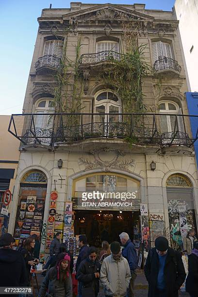 Tourists walk in front of a shopping arcade in San Telmo neighborhood in Buenos Aires Argentina on June 14 2015 San Telmo is one of the oldest...