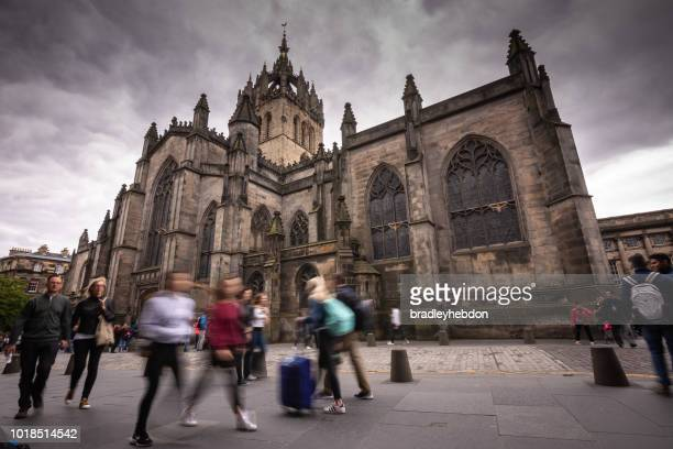 Tourists walk in front of St Giles' Cathedral in Edinburgh, Scotland