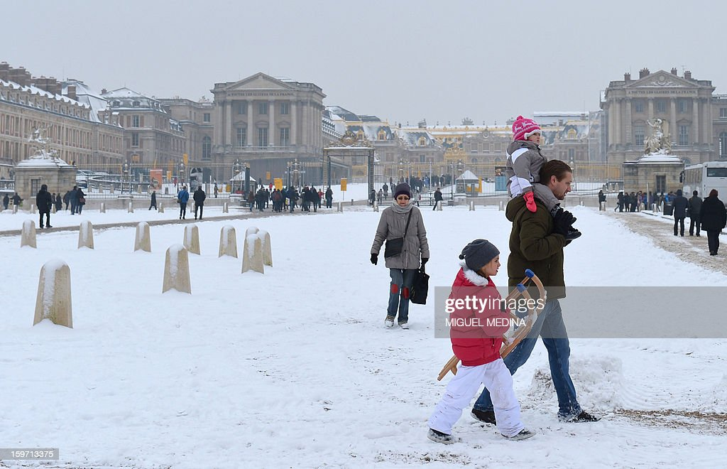 Tourists walk in front of the Chateau de Versailles on January 19, 2013 in Versailles, after heavy snowfall overnight.