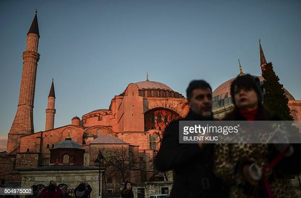Tourists walk in front of the Hagia Sofia museum on January 14 2016 near the makeshift memorial in tribute to the victims of January 12 deadly attack...