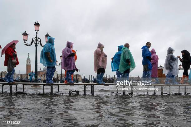 Tourists walk in high water Piazza San Marco in Piazza San Marco on November 12 2019 in Venice Italy High tide or acqua alta as it is more commonly...