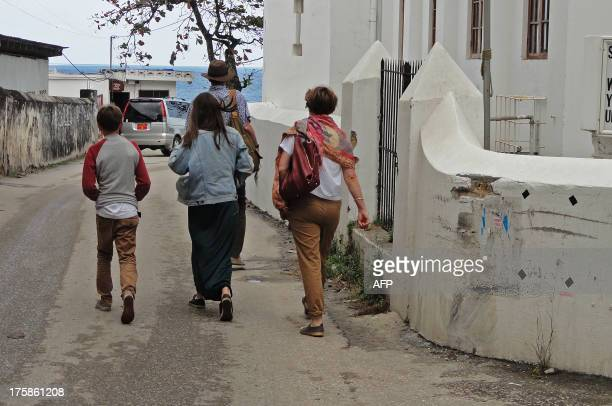 Tourists walk in Stone Town past the spot where two young British women suffered an acid attack on the Indian Ocean island of Zanzibar on August 9...
