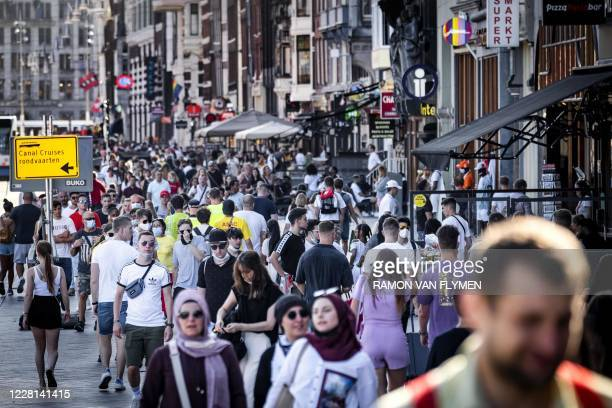 Tourists walk in the center of Amsterdam on August 21, 2020 as the Netherlands tighten up supervision of the measures to prevent further spread of...
