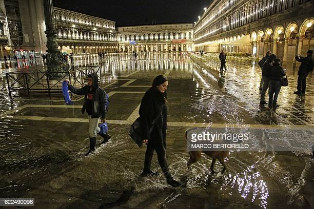 Tourists walk in the flooded St Mark's square during a night of acquaalta or highwater in Venice northern Italy on November 11 2016 / AFP / MARCO...