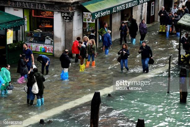 Tourists walk in the flooded street near Rialto Bridge during a acquaalta alert in Venice on October 29 2018 The flooding caused by a convergence of...