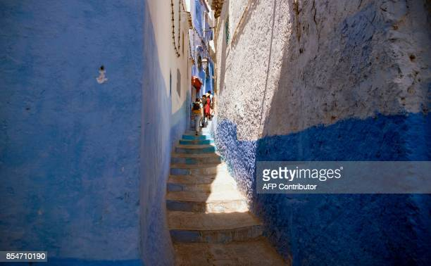 Tourists walk in the Medina of the northwestern Moroccan city of Chefchouen in the northern Rif region on September 21 2017 / AFP PHOTO / FADEL SENNA