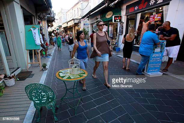 Tourists walk in the quiet main shopping street of Mythelini on July 19 2016 on Lesvos island Greece The increase in refugees arriving on the island...