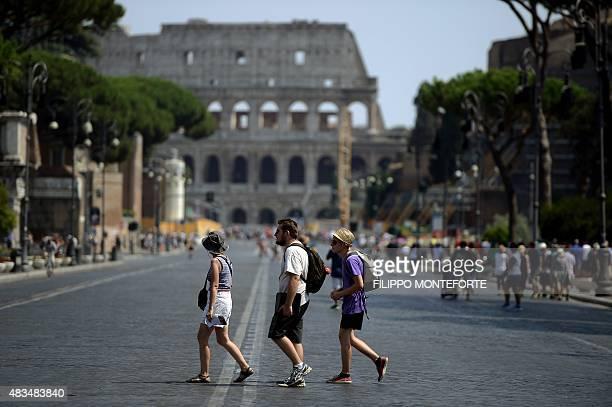 Tourists walk in the street Via dei Fori Imperiali near the Colosseum in central Rome on August 9 2015 AFP PHOTO / FILIPPO MONTEFORTE