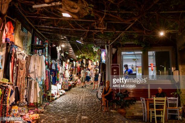 Tourists walk in the streets of Mithymna in the northeastern island of Lesbos on August 3 2018