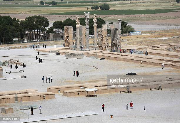 Tourists walk near ancient ruins of the Gate of All Nations at the Persepolis archeological site on May 30, 2014 in Persepolis, Iran. The ruins mark...