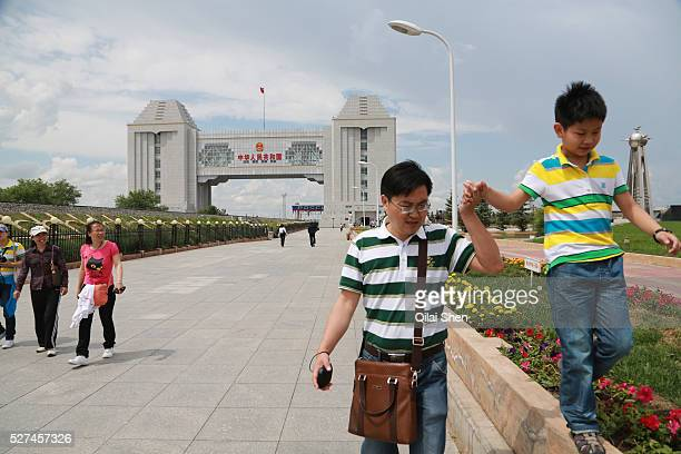 Tourists walk near the National Gate, a border crossing between China and Russia, in Manzhouli, Inner Mongolia, China, on 30 June, 2012. Manzhouli...