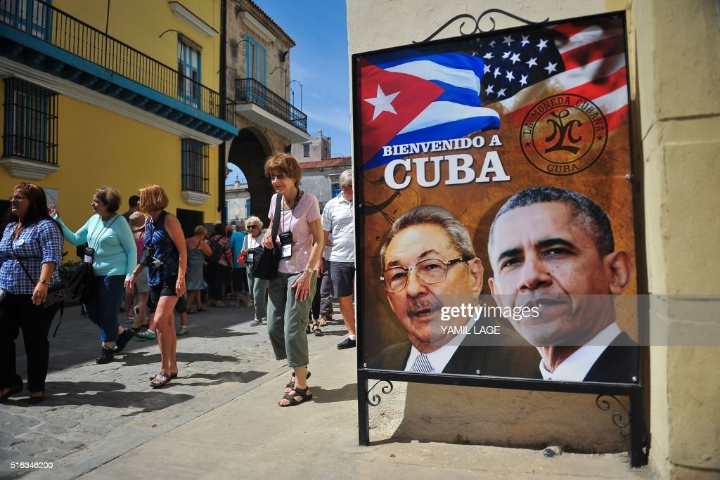 Tourists walk next to a poster of Cuban President Raul Castro and US president Barack Obama in Havana, on March 18, 2016. US president Barack Obama touches down in Havana on Sunday to cap a long-unimaginable rapprochement with Cuba and burnish a presidential legacy dulled by Middle East quagmires and partisan sniping. As Air Force One rolls to a stop, Obama will become the first sitting US president to visit Cuba since Calvin Coolidge arrived on a battleship in 1928, before the discovery of penicillin or invention of the ballpoint pen.