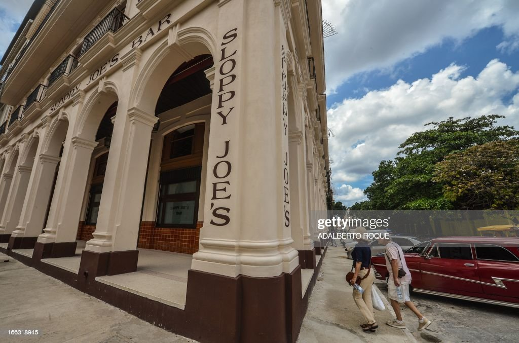 Tourists walk next to the newly renovated 'Sloppy Joe's' bar in Havana, on April 11, 2013