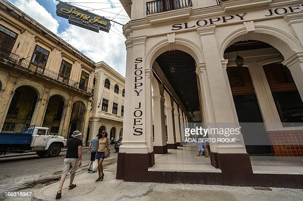 Tourists walk next to the newly renovated Sloppy Joe's bar in Havana on April 11 2013 Sloppy was one of the most famous places in the...