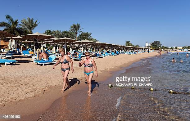 Tourists walk olong a beach in Egypt's Red Sea resort of Sharm ElSheikh on November 10 2015 As visitors stranded after the crash of a Russian...