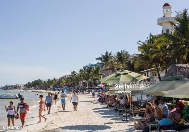 Tourists walk on a beach in Playa del Carmen Mexico on Tuesday July 11 2017 The narcotraffickers already hold sway over swaths of Mexico either...