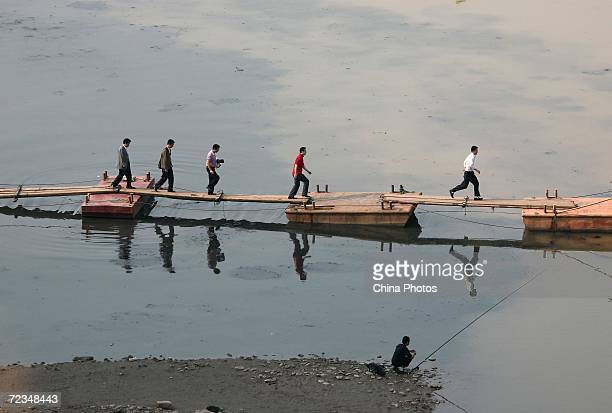 Tourists walk on a floating bridge on the polluted Jialing River on November 2 2006 in Chongqing Municipality China China will make an allout effort...
