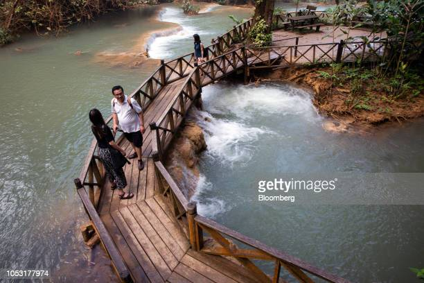 Tourists walk on a footbridge at the Kuang Si Waterfall in Luang Prabang Province Laos on Sunday Oct 21 2018 Laos's economy is set to expand at 7...