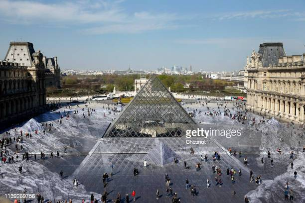 Tourists walk on a giant photographic work by French photographer and artist Jean Rene, known as JR in the main courtyard Cour Napoleon of the Louvre...
