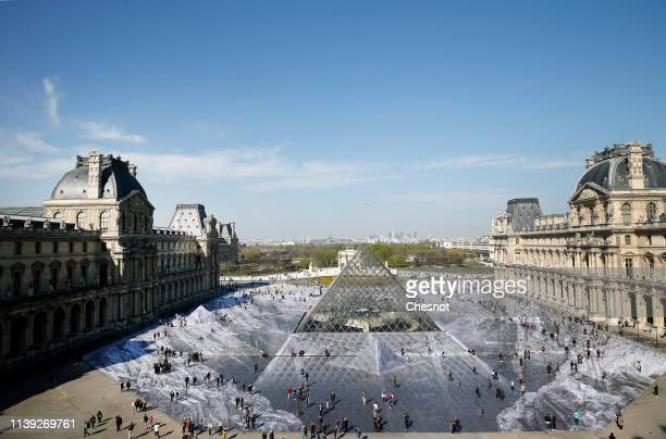 Tourists walk on a giant photographic work by French photographer and artist Jean Rene known as JR in the main courtyard Cour Napoleon of the Louvre...