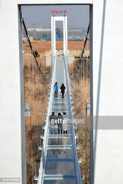 Tourists walk on a glassbottomed skywalk at Yibin District on February 7 2018 in Luoyang Henan Province of China The glass walkway stretches 138...