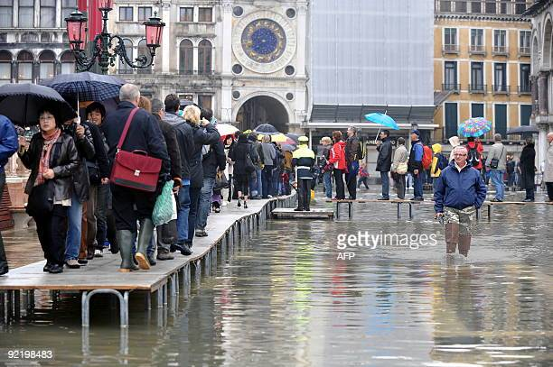 Tourists walk on a platform on the flooded Piazza San Marco on October 22 2009 in Venice The acqua alta a convergence of high tides and a strong...