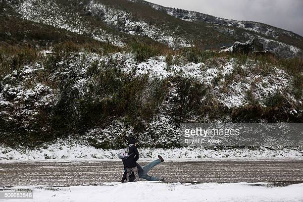 Tourists walk on a slippery section of ice as snow is seen on the Yangmungshan National Park during a snowfall on January 25 2016 in Taipei Taiwan...