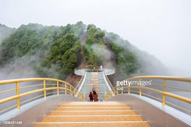 Tourists walk on cloud-shrouded Ruyi Bridge at Shenxianju Scenic Area on March 9, 2021 in Taizhou, Zhejiang Province of China.