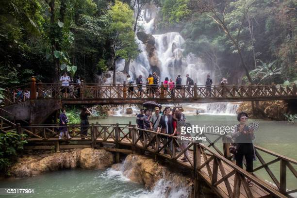 Tourists walk on footbridges at the Kuang Si Waterfall in Luang Prabang Province Laos on Sunday Oct 21 2018 Laos's economy is set to expand at 7...