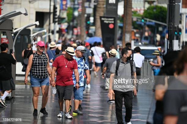 Tourists walk on Hollywood Boulevard's Walk of Fame, August 16, 2021 in Hollywood, California. - Tourism on Hollywood Boulevards has increased as...