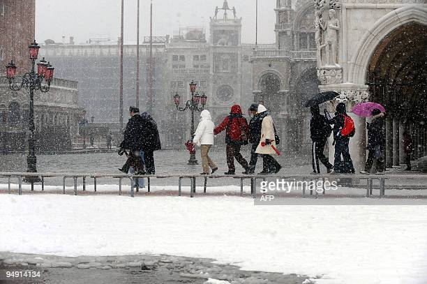 Tourists walk on platforms on the flooded Piazza San Marco covered with snow on December 19 2009 in Venice The acqua alta a convergence of high tides...