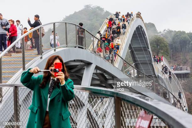 Tourists walk on Ruyi Bridge at Shenxianju Scenic Area on March 9, 2021 in Taizhou, Zhejiang Province of China.
