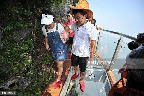 Tourists walk on the 100meterlong and 16meterwide glass skywalk clung the cliff of Tianmen Mountain in Zhangjiajie National Forest Park on August 1...