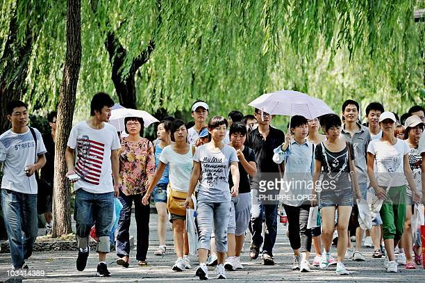 Tourists walk on the banks of the West Lake in the popular tourist destination of Hangzhou on August 17 2010 Famous for its beautiful natural scenery...