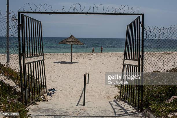 Tourists walk on the beach past the beach gates of the closed Imperial Marhaba Hotel on June 24 2016 in Sousse Tunisia The Imperial Marhaba hotel was...