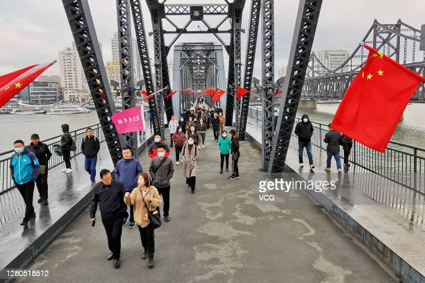 Tourists walk on the Broken Bridge decorated with Chinese flags over the Yalu river on October 15, 2020 in Dandong, Liaoning Province of China.