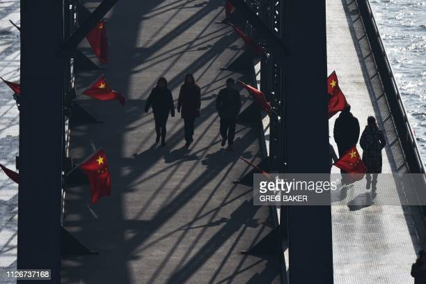 Tourists walk on the Broken Bridge, which once spanned the Yalu River between China and North Korea, in the Chinese border city of Dandong, in...