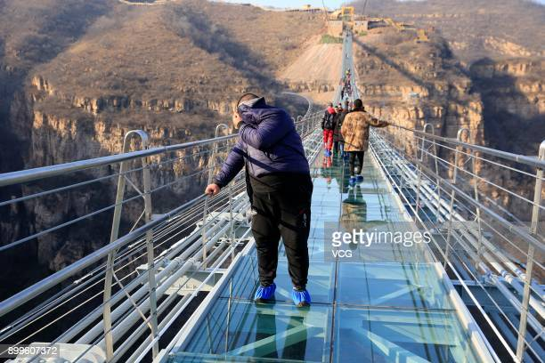 Tourists walk on the glass-bottomed suspension bridge at Hongyagu Scenic Area on December 26, 2017 in Pingshan, Hebei Province of China. The...